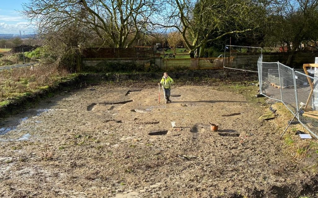 Image: archaeologist stands in 9m Iron Age roundhouse footprint
